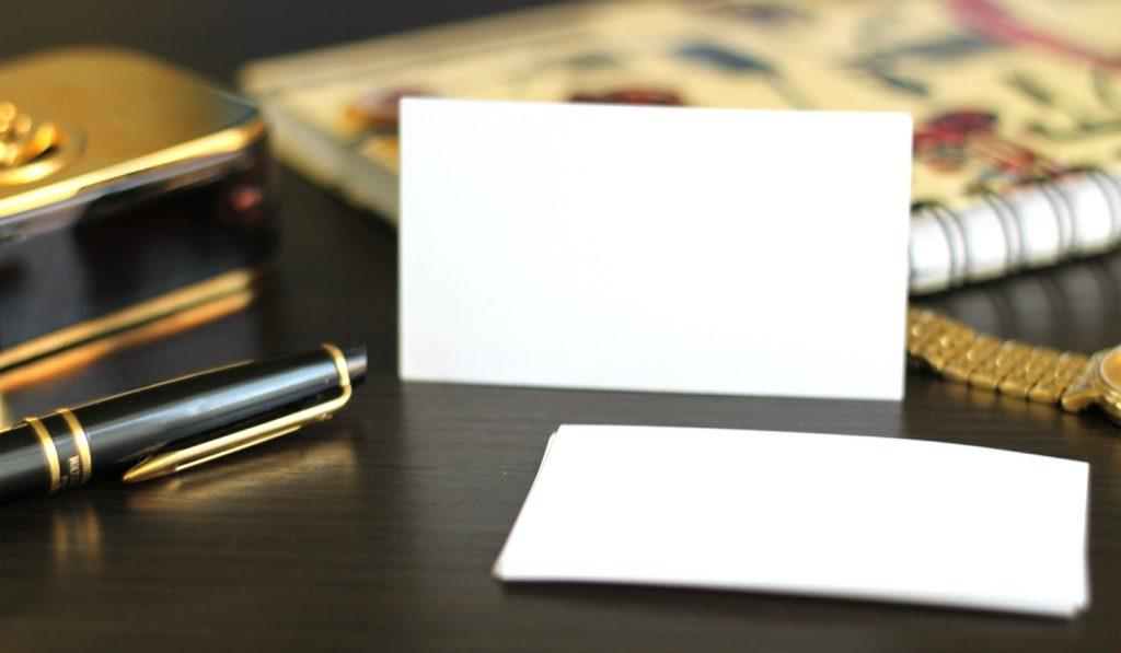una scrivania con biglietti da visita un orologio e una penna